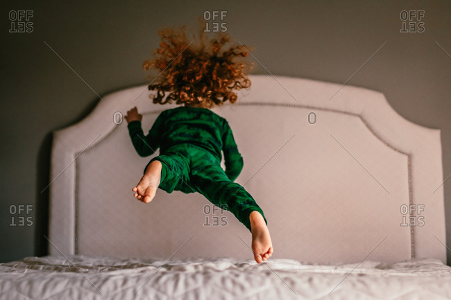 Red haired child jumping on bed