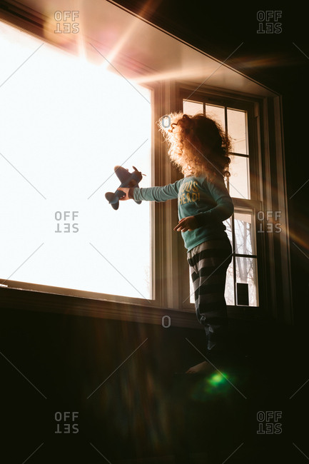 Child flying toy airplane in window