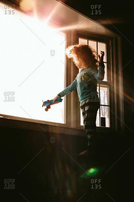 Child playing with toy airplane in window
