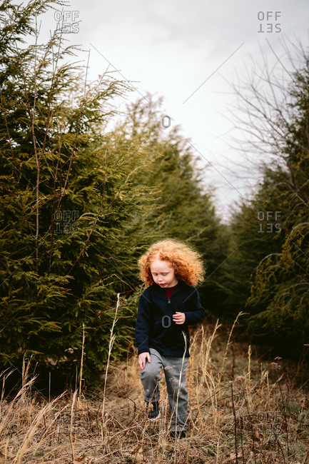 Child with long red hair walking between trees