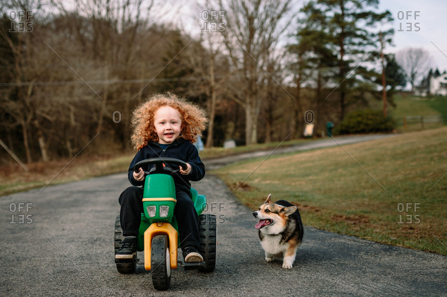 Child riding toy tractor with dog trotting along