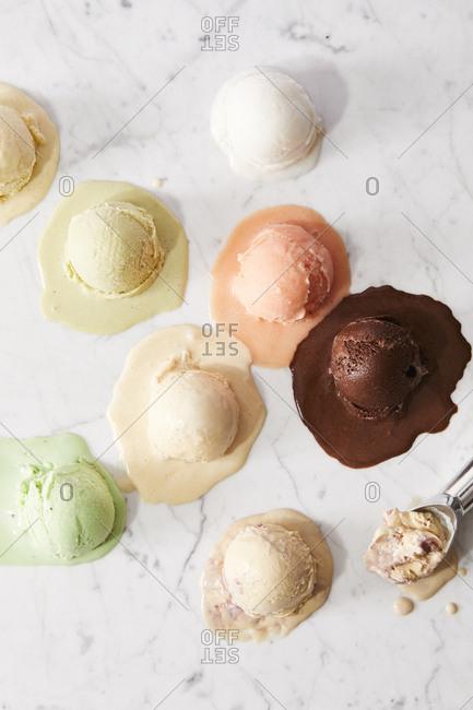 Melting scoops of ice cream melting on marble surface