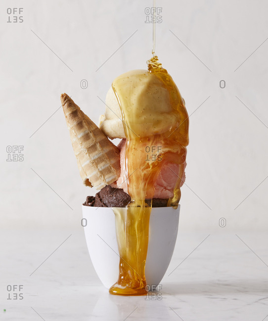 Dish of ice cream with cone and honey
