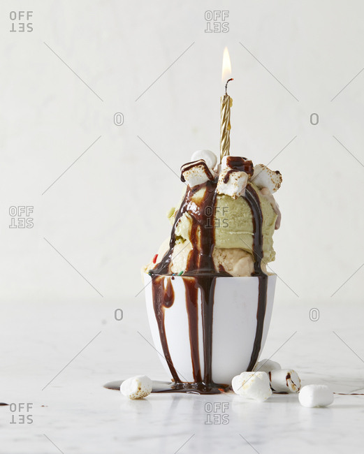 Two scoops of ice cream in dish with candle and chocolate sauce