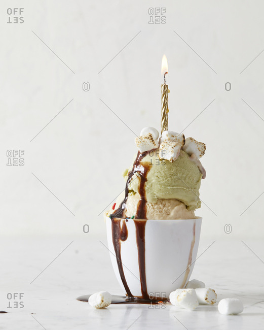 Double scoop of ice cream in dish with candle and chocolate sauce