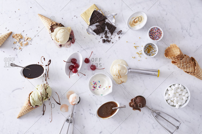 Arrangement of ice cream with toppings on white marble