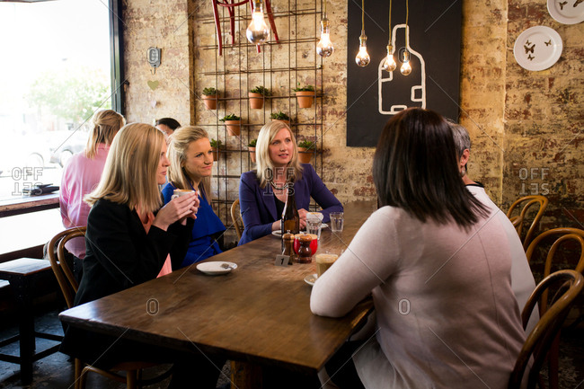 Women meeting around table at coffee shop