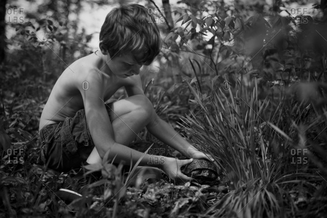 Boy picking up a turtle outside