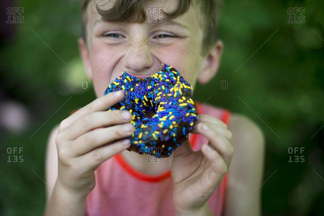 Boy eating a doughnut outside
