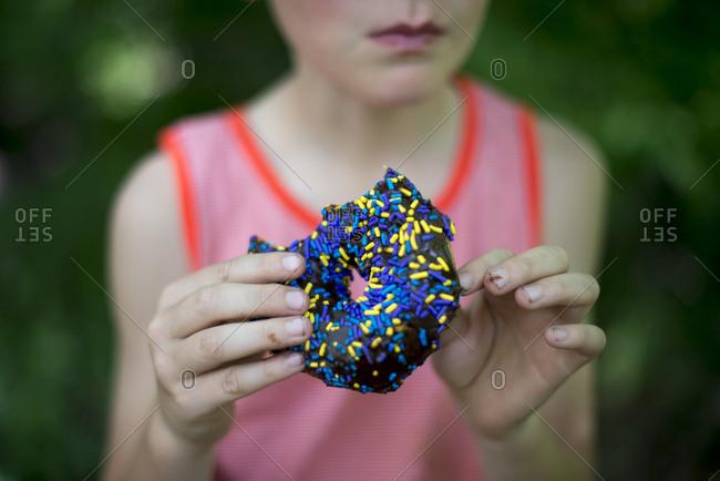Boy holding sprinkled doughnut outside