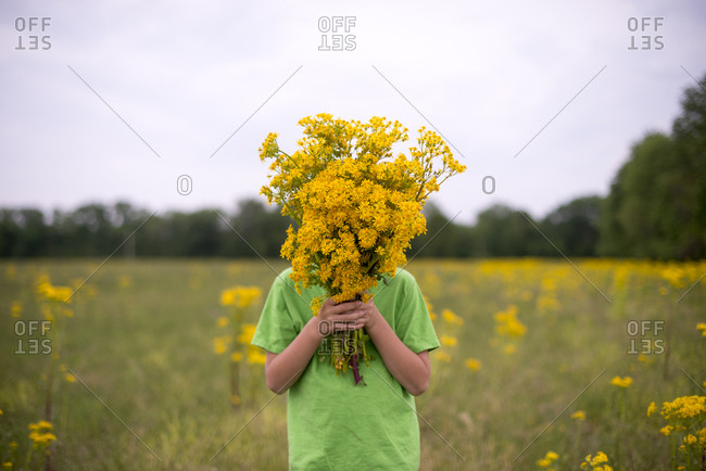 Boy covering face with wildflowers
