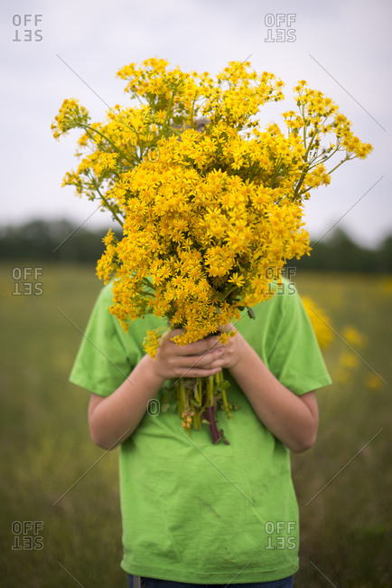 Boy covering his face with wildflowers