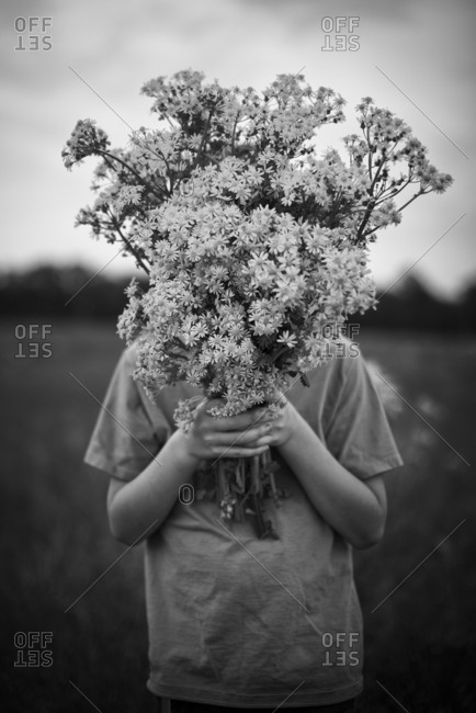 Boy with face covered by wildflowers