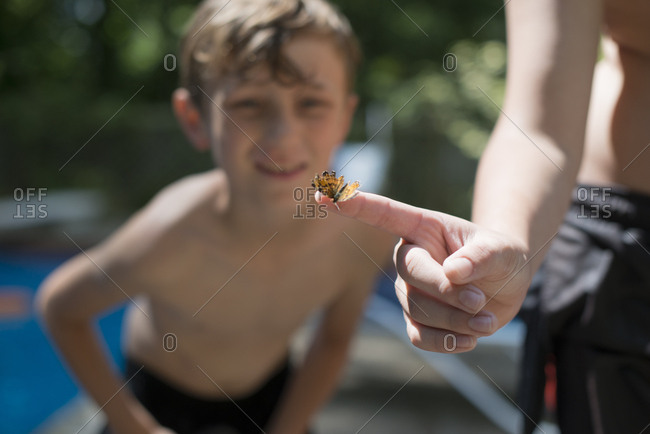 Boy looking at butterfly on finger