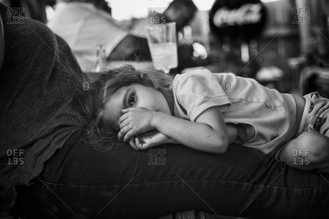 Girl lying on woman's legs