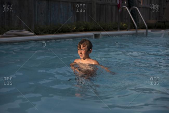 Boy in backyard swimming pool