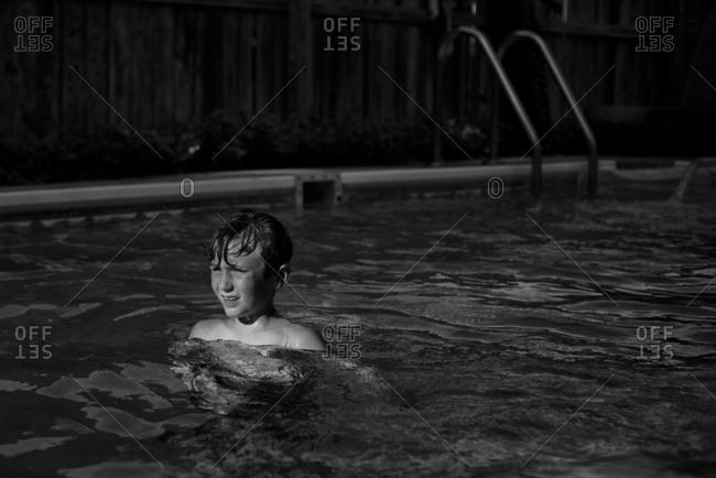 Boy standing in backyard swimming pool