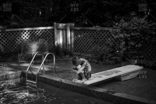 Boy hiding his face on diving board