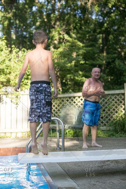 Senior man and boy at backyard pool