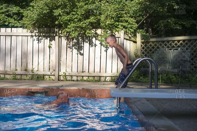 Senior man and boy in a pool