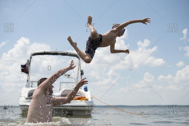 Man throwing boy into lake