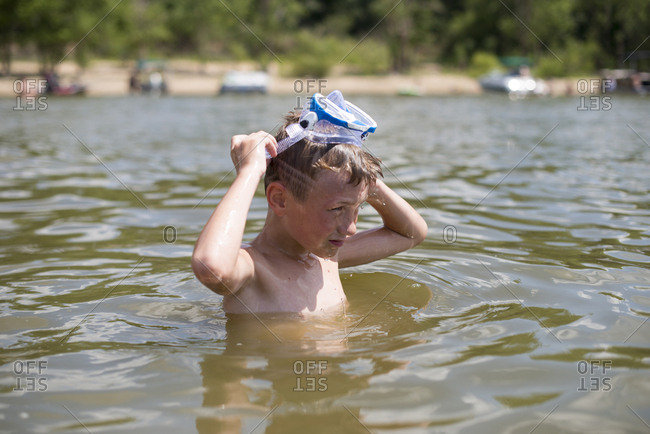 Boy with snorkel mask in a lake