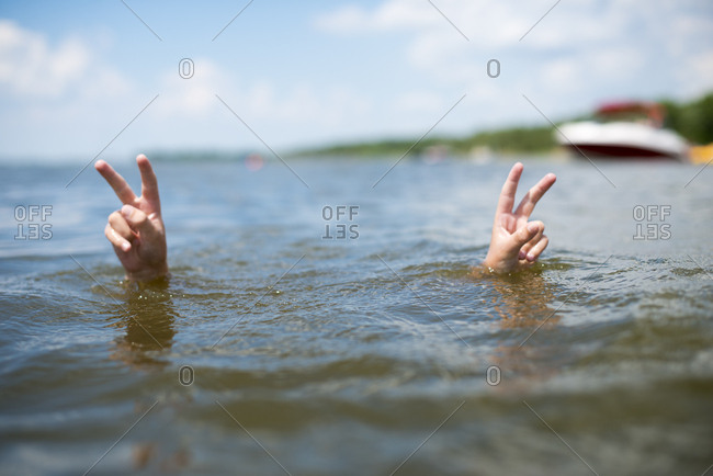Boy making peace signs in water