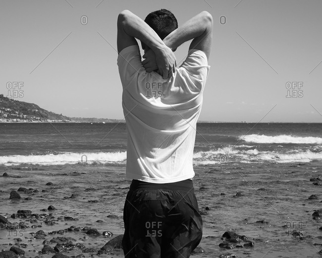 Man stretching arms by sea