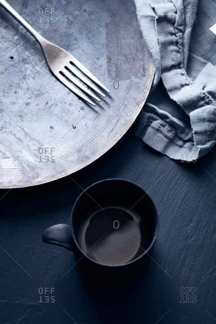 Empty mug next to metal plate