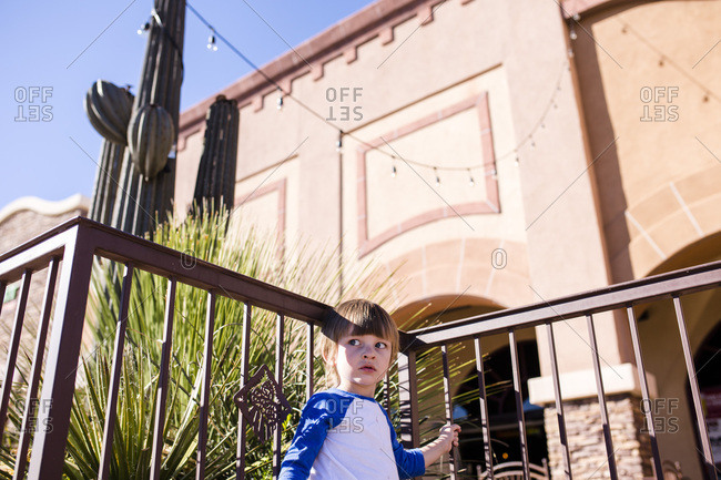 Boy standing at a railing near a Southwestern style building