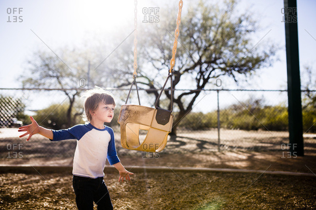 Boy standing on a playground playing with a bucket swing