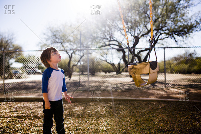 Little boy at a park looking at a swing