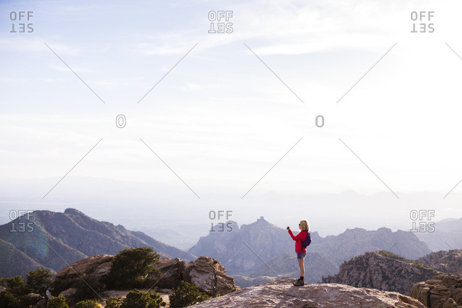 Girl standing on a mountain top taking a photograph