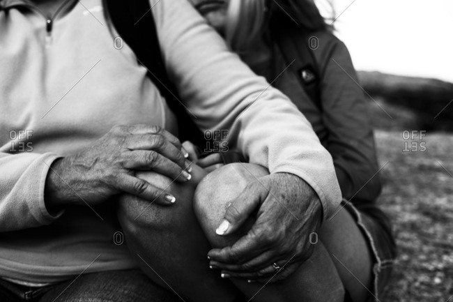 Hands of a grandmother on her granddaughter's knees as they sit together