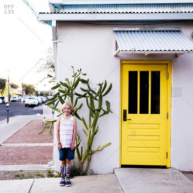 Girl smiling playfully near a building with a bright yellow door and cactus