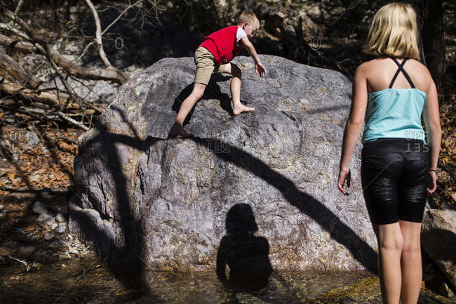 Boy climbing a rock beside a stream while his sister watches him