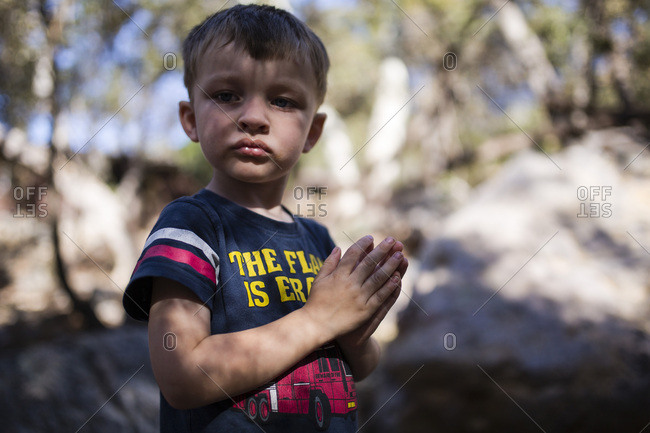 Little boy standing in the woods with his hands clasped together