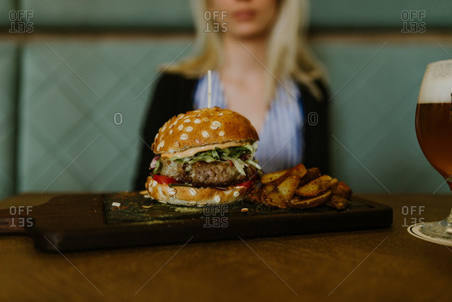 Burger and fries on a table in front of a woman at a restaurant