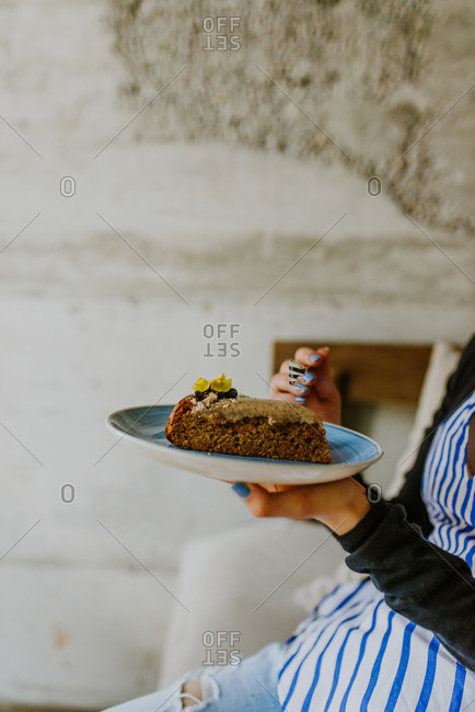 Woman holding a plate with a piece of cake