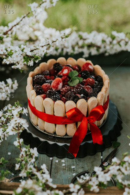 Cake with berries and cookies around the edges on a rustic wooden tray