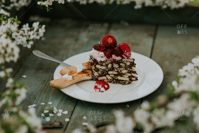 Partially eaten berry cake on a rustic tray with cherry blossoms