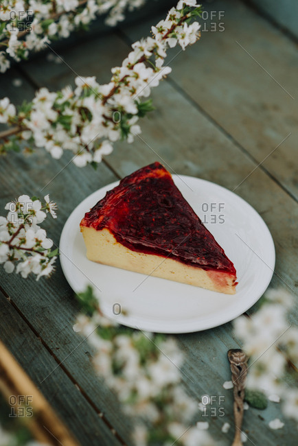 Slice of cheesecake with berry topping on a rustic wooden tray