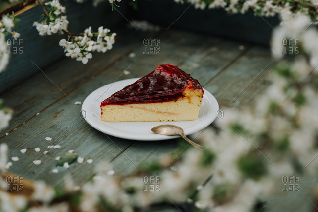 Cheesecake with berry topping on a rustic wooden tray with cherry blossoms