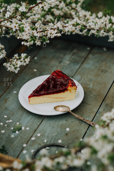 Cheesecake topped with berries on a rustic wooden tray