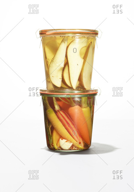 Two jars with carrots and pear slices in liquid