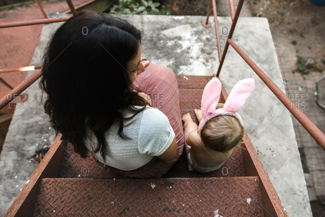 Mom and baby sit outside on fire escape while wearing bunny ears