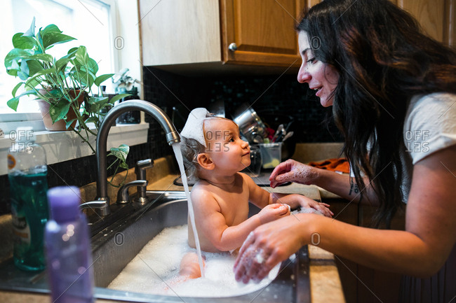 Mom giving baby a bubble bath in kitchen sink
