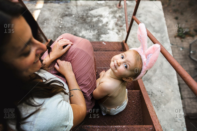 Mom and diapered baby sit outside on fire escape while wearing bunny ears