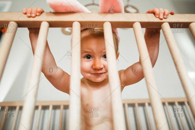 Baby peeking through crib bars