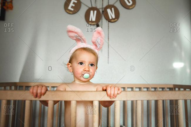 Baby standing in crib wearing bunny ears